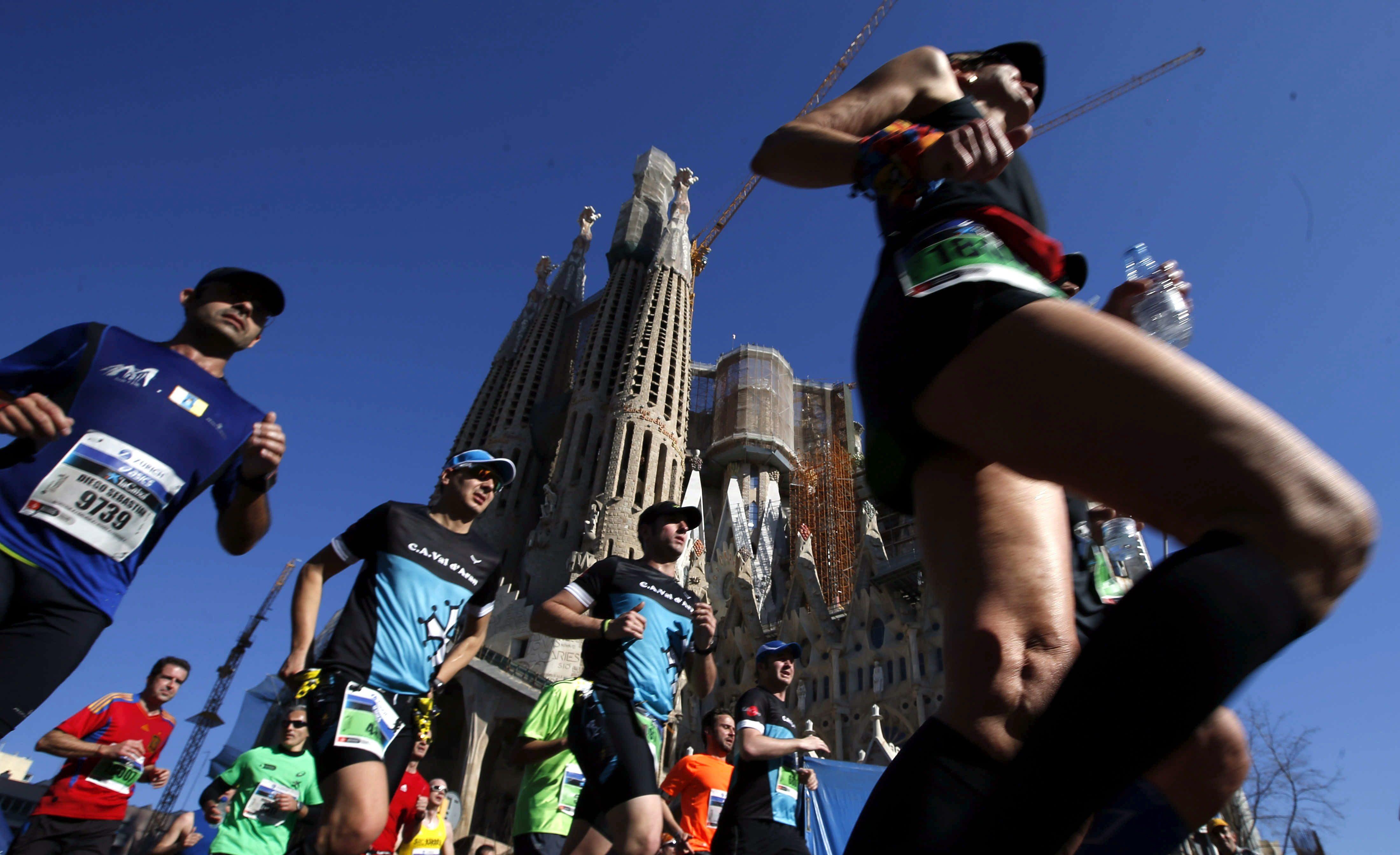 GRA036. BARCELONA, 16/03/2014.- Un grupo de corredores pasan ante la Sagrada Familia durante la trigésimo cuarta edición del Maratón de Barcelona, en la que participan 17.830 atletas de 87 países, lo que la sitúa entre las cinco 'grandes' de Europa. EFE/Alberto Estévez